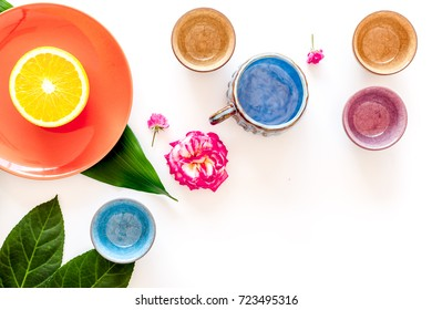 Tableware pattern. Cups and plates decorated by exotic leaves and fruits on white background top view