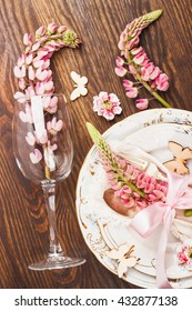 Tableware with pink lupines, silverware and decorations on the wooden background