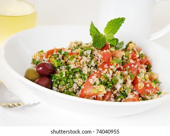Tabouli salad in white bowl with coffee mug and glass of wine