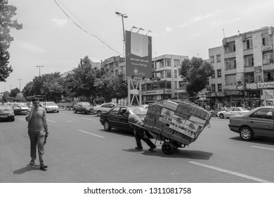 Tabriz, Iran - 10 July 2017: Street of Iran with a  carrier in the middle of the road with cars around. Guy delivering cardbox in the way