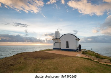 Tacking Point Lighthouse sunrise with people looking sunset. Por