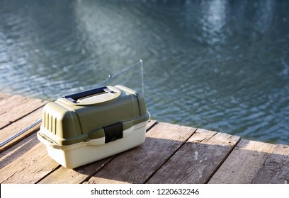 Tackle box and rod for fishing on wooden pier at riverside. Recreational activity