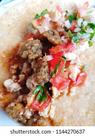 Taco beef, tomato and onion on a Mexican tortilla.