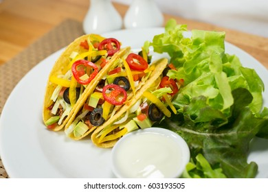 Taco with meat vegetables on white plate