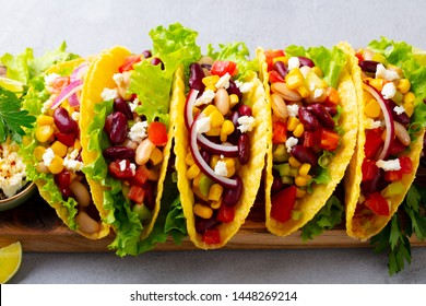 Taco with mixed vegetables, beans on cutting board. Grey background. Close up.