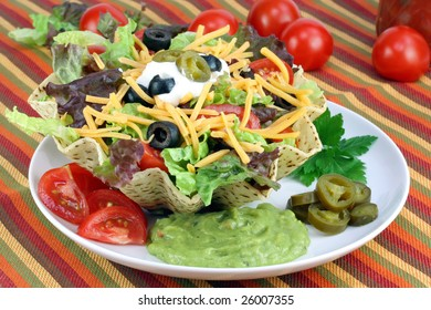 Taco salad in a corn taco bowl surrounded with tomatoes, jalapeno peppers and guacamole.
