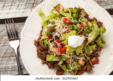 Taco salad on an antique platter on a weathered barn wood table angled view