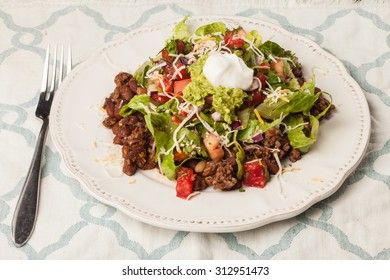 Taco salad on an antique platter on a blue and white place mat