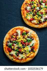 Taco vegetarian pizza. Mexican pizza with beans, corn, jalapeno pepper, mozzarella cheese on a dark background, top view. Snack, snack, tapas