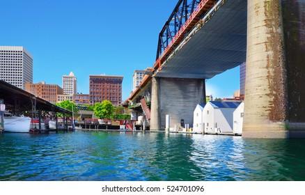 Tacoma downtown city marina with houses under large bridge.