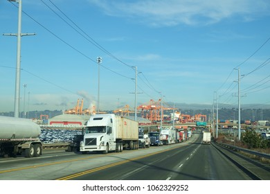 Tacoma, WA, USA Jan. 23, 2017: Long line of semi trucks leaving Port of Tacoma shipping terminals with orange cranes in background