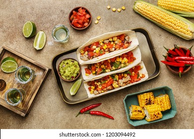 Tacos with chicken, tomatoes and corn with guacamole sauce, lime, corn cobs, grilled corn, chili peppers and tequila shots on beige concrete background. Overhead view, flat lay. Mexican party snacks