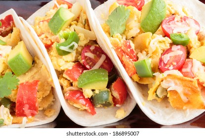 Tacos filled with migas, a Tex-Mex dish of eggs scrambled with red bell pepper, onions, jalapenos, cheese, topped with avocado, cilantro, cherry tomatoes