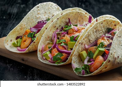 Tacos made of prawns, avocado, red onion, cabbage and lime on a table. Delicious Mexican cuisine meal.