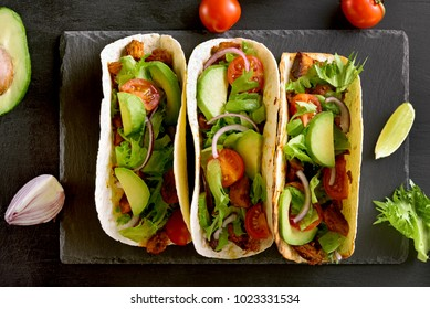 Tacos with meat and vegetables on black stone background. Top view, flat lay