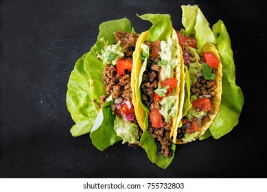 tacos with minced meat filling, lettuce and guacamole on a dark slate background, top view from above, copy space, selected focus