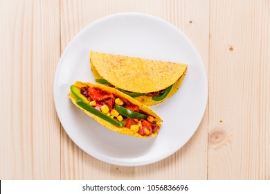 Tacos on a white plate, on wooden table, top view