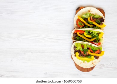 Tacos with pork and vegetables. Mexican kitchen. White wooden  background. Top view, flat, overhead. Copy space and text area.
