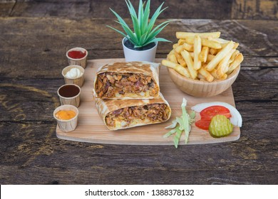 Tacos sandwich accompanied with french fries, tomato, pickle. Served on a wooden board on a wooden design table.