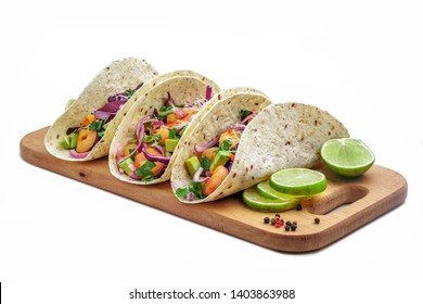 Tacos with shrimps., avocado and red onion on a wooden table. Traditional American fast food. Studio shot, isolated on white background.
