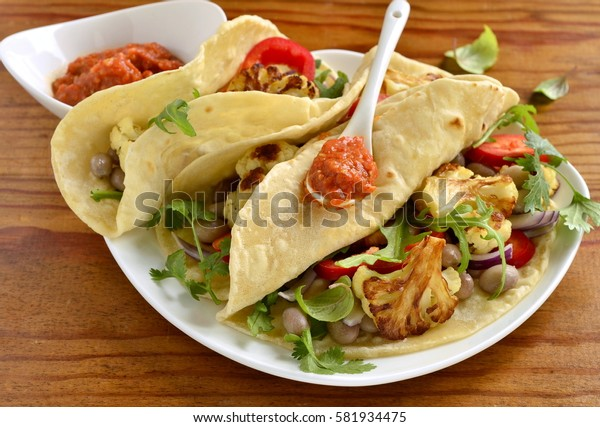 Tacos, tortilla with roasted cauliflower, beans, vegetables and sauce
