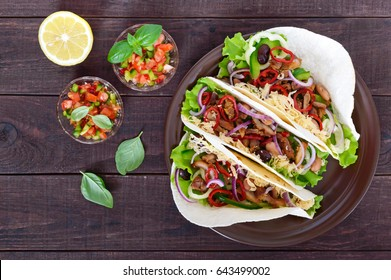 Tacos is a traditional Mexican dish. Tortilla stuffed with chicken, bell and hot peppers, beans, lettuce, cheese, blue onion with salsa sauce on dark wooden background. Top view.