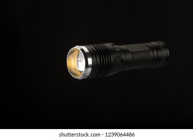 Tactical flashlight, hand on black background, studio light