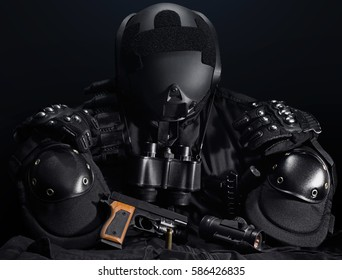 Tactical gear composition. Black military tactical gun, helmet, glowes, cartridge belt, bandolier, gun shell, knife, binocular and knee protection laying on a black table.