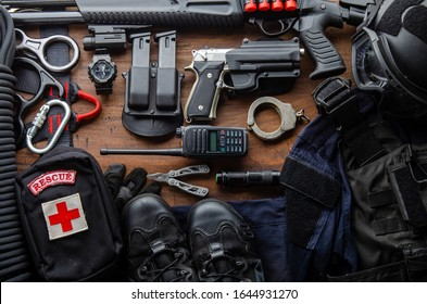 Tactical gear equipment Special forces soldier police Spec ops officer SWAT. Black military ammunition tactical gun, helmet, gloves, shotgun, pistol, accessory on Wooden background Top view copyspace