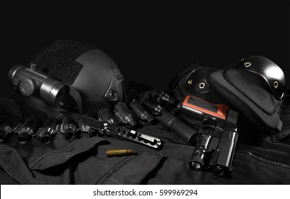 Tactical gear laying composition. Black military ammunition tactical gun, helmet, gloves, cartridge belt, bandolier, gun shell, knife, binocular and knee protection laying on a black table.