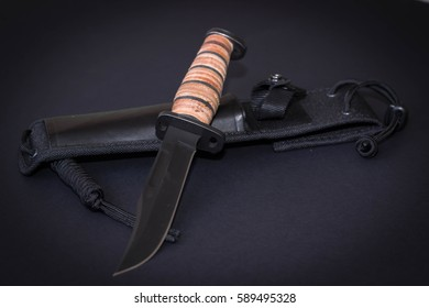 Tactical knife with sheath on black background