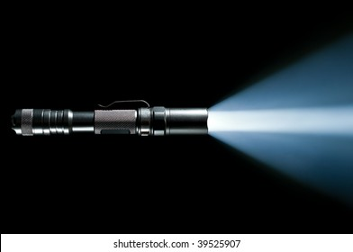 tactical police and military flashlight on black background with visible beam of light