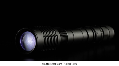 tactical police and military flashlight on black background.