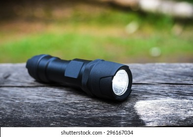 Tactical waterproof flashlight on wooden base with light beam