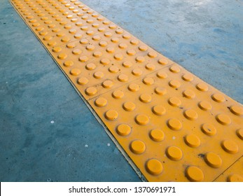 Tactile Paving or Tenji Block on Ground Surface as Guidance or Detectable Warning to Help Pedestrians who Visually Impaired or Blind. Yellow Truncated Domes Walking Indicator