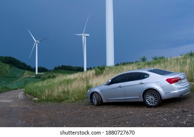 Taebaek-si, Gangwon-do, South Korea - August 5, 2015: K7 of KIA Motors is packed on dirt road among cabbage field and wind power plant at Gwynemi Village