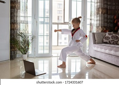 Taekwondo girl in kimono with white belt exercising at home in living room. Online education during coronavirus covid-19 lockdown, self isolation and social distancing concept