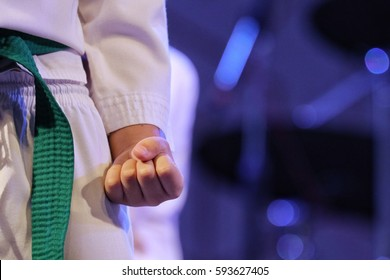 Taekwondo kid player make fist of left hand at beside the hip, wear taekwondo white uniform and green belt. Background is blur fist of other player, image blue tone from blue light decoration of stage