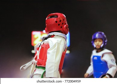 Taekwondo Kids action with uniform and green belt. Double exposure another player during the tournament taekwondo kids in stadiums.