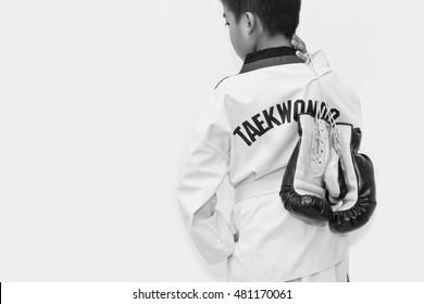 Taekwondo kids hold boxing gloves on white background.