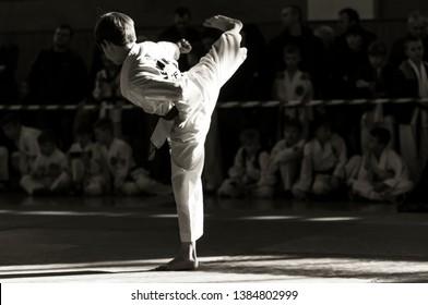 "Taekwondo martial art. A young man in kimano demonstrates a kick. The inscription on the jacket ""Taekwondo"""