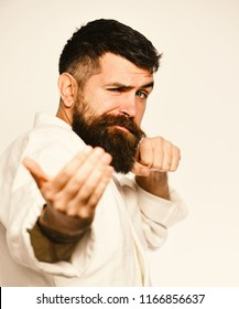 Taekwondo master practices attack and provokes fight. Man with beard in white kimono on white background. Oriental sports concept. Karate man with flirty face in uniform.
