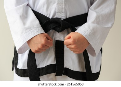 Taekwon-do woman with black belt, 1e dan, getting ready for training.