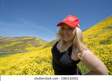 Taft, CA - March 25, 2019: Blonde republican woman wears a Donald Trump Make America Great Again hat, standing in a field of yellow wildflowers. Concept for 2020 United States President Election
