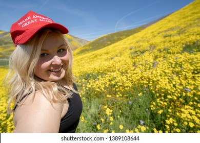 Taft, California - March 25, 2019: Blonde republican woman wears a Donald Trump Make America Great Again hat in a field of yellow wildflowers. Concept for the 2020 United States Presidential Election