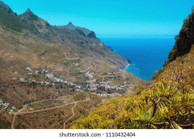 Taganana village with white houses and serpentine road in green Anaga mountain  in Tenerife, Canary Islands. Spain. Taganana valley and Atlantic ocean landscape background.