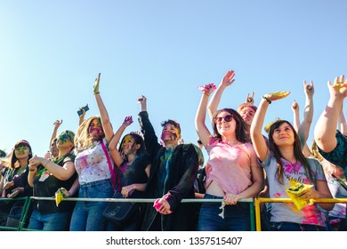 TAGANROG, RUSSIAN FEDERATION - June 02, 2018.Crowd of young teenager  , faces smeared with colors   raising hands . Concept for Indian colours festival Holi or the festival of sharing love