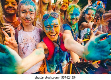 TAGANROG, RUSSIAN FEDERATION - June 04, 2016. Young teenager, faces smeared with colors and raising hands. Concept for Indian colours festival Holi or the festival of sharing love