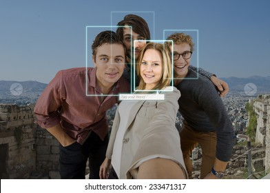Tagging and sharing a friend in a selfie of four people using facial recogintion software applications in front of a large city for sharing on varous social media platforms