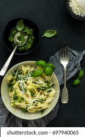Tagliatelle with basil pesto sauce,fresh basil (close-up) and grated Parmesan cheese in bowl on dark slate background. Italian cuisine background with Basil Pesto, Pasta dish and cheese. Top view.